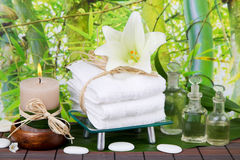 Asian massage oil with candle, towels and lily Royalty Free Stock Image