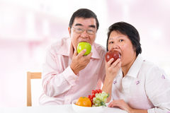 Asian mature couple eating apple Royalty Free Stock Photos