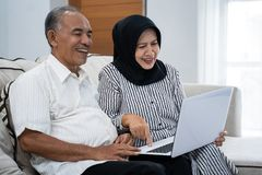 Asian mature couple enjoying a modern technology by a laptop royalty free stock images