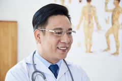 Asian smiling mature doctor. Asian mature male doctor in eyeglasses and white lab coat standing at hospital and smiling stock photo