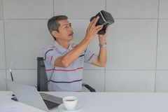 Asian Mature man, Holding VR glasses for testing new modern technology. Front on the desk. there are white coffee mug and laptop computer, pen in the office stock photography