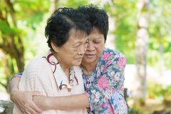 Asian mature woman hugs and consoling her crying old mother. Candid shot of an Asian mature women hugs and consoling her crying old mother at outdoor natural stock photo