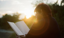 Asian mature woman reading a book at sunset moment.blurred sunset in background.silhouette woman read the book Stock Photography