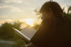 Asian mature woman reading a book at sunset moment.blurred sunset in background.silhouette woman read the book. Royalty Free Stock Photography