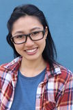 Asian mature woman smiling happy wearing glasses. Beautiful young Asian woman isolated on blue background Royalty Free Stock Photo
