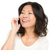 Asian mature woman talking on mobile phone. Middle aged Asian woman on smartphone. Beautiful mature Chinese Asian woman talking on mobile phone isolated on white royalty free stock photography