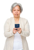 Asian mature woman use of cellphone Royalty Free Stock Photography