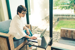 Asian mature woman using laptop with smartphone and coffee at cafe, vintage tone, middle aged adult with modern gadget technology stock photography