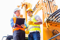 Asian mechanic with construction machine Stock Images