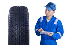 Asian mechanic controls a tire with tablet. Young technician with a blue uniform, using a digital tablet to control a tire Stock Photo