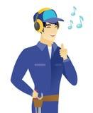 Asian mechanic listening to music in headphones. Royalty Free Stock Photo