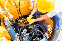 Asian mechanic repairing construction vehicle Stock Images