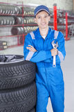 Asian mechanic with wrench and arms folded. Portrait of a young Asian mechanic standing in the workshop and leans on the tires while holding a wrench stock images