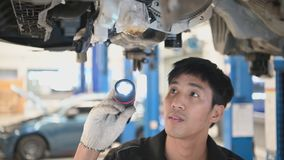 Asian mechanical hold and shining flashlight to examine car disk brake pad wear of automotive vehicle. Safety suspension. Inspection check service maintenance stock footage
