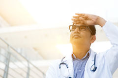 Asian medical doctor. Portrait of Asian Indian medical doctor hand shielded looking away, standing outside hospital building, beautiful golden sunlight at Royalty Free Stock Photography