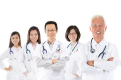 Asian medical team. Expertise senior and mature doctors leading young practitioners, standing isolated white background Stock Photography