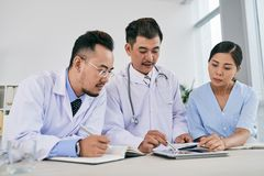 Discussing diagnosis. Asian medical team reading medical history to make diagnosis stock photography