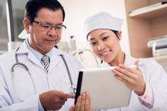 Asian medical workers. Young women intern showing doctor some information on a digital tablet Stock Image