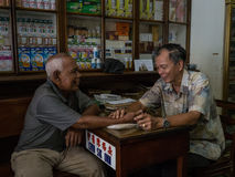 Chinese Medicine Consultation. A Chinese Doctor consults a patient in a traditional Asian Apothecary in the old town of Melaka, Malaysia Royalty Free Stock Photo