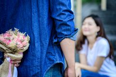 Asian man has preparing and waiting with flower for say sorry an. Asian men has preparing and waiting with flower for say sorry and apologies to girlfriend Royalty Free Stock Photography