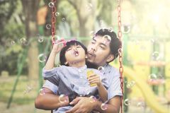 Asian man with child blowing soap bubbles Royalty Free Stock Images
