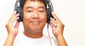 Asian men relaxing with music on holiday. Asian man relaxing with music on holiday show on a white background Stock Photo