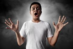Asian men scared on smoke background. Asian man scared on smoke background Royalty Free Stock Photography