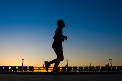 Asian men are silhouette jogging at a speed in the evening. Stock Photography