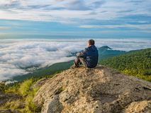 Asian men Sit on the cliff with beautiful sky on Khao Luang mountain in Ramkhamhaeng National Park. Asian man Sit on the cliff with beautiful sky on Khao Luang royalty free stock photography