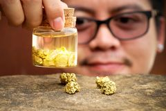 Asian men smiling and looking at gold in the bottle royalty free stock images