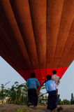 Asian Men standing in front of hot air balloon over Bagan Stock Photo