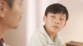 Asian father talking & counseling his frustrated teenage boy at Royalty Free Stock Photos
