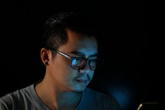 Asian men are using the phone or tablet with a blue light in the darkness, Royalty Free Stock Photos
