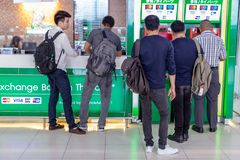 Asian men waiting in line to withdraw money from bank`s ATM mach. Bangkok, Thailand - 21 July 2018 - Asian men wait in line patiently to use the ATM mahine at royalty free stock photography