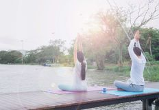 Asian men and women meditate and yoga at the waterfront on a woo royalty free stock photos