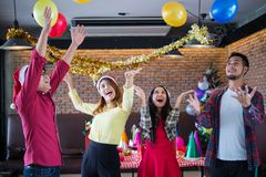 ASian man and woman wear santa claus hat having fun in Christmas party,dancing and playing balloons at the restaurant,. Asian men and women wear santa claus hat royalty free stock photography