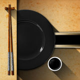 Asian Menu with Wooden Chopsticks. Template for an Asian menu with wooden and silver chopsticks, black plate and a bowl of sauce. Black band with space for text Royalty Free Stock Image