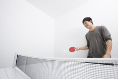 Asian mid adult man playing ping-pong Stock Images