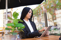 Asian middle-aged businesswoman working at a cafe table Stock Images