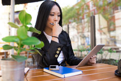 Asian middle-aged businesswoman working at a cafe table Royalty Free Stock Image