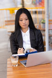 Asian middle-aged businesswoman working at a cafe table Royalty Free Stock Photography