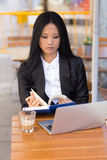 Asian middle-aged businesswoman working at a cafe table Stock Photo
