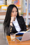 Asian middle-aged businesswoman working at a cafe table Stock Photos