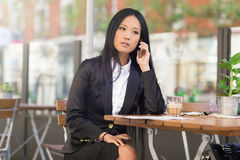 Asian middle-aged businesswoman working at a cafe table. Asian middle-aged businesswoman sitting at a cafe table talking on the phone Royalty Free Stock Image