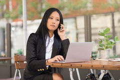 Asian middle-aged businesswoman working at a cafe table. Asian middle-aged businesswoman sitting at a cafe table using a laptop computer and talking on the phone Stock Images