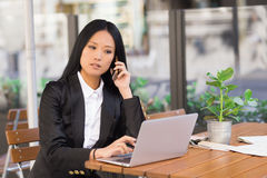 Asian middle-aged businesswoman working at a cafe table. Asian middle-aged businesswoman sitting at a cafe table using a laptop computer and talking on the phone Royalty Free Stock Images