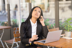 Asian middle-aged businesswoman working at a cafe table. Asian middle-aged businesswoman sitting at a cafe table using a laptop computer and talking on the phone Royalty Free Stock Photos