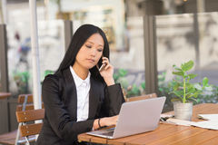 Asian middle-aged businesswoman working at a cafe table. Asian middle-aged businesswoman sitting at a cafe table using a laptop computer and talking on the phone Royalty Free Stock Photo