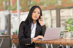 Asian middle-aged businesswoman working at a cafe table. Asian middle-aged businesswoman sitting at a cafe table using a laptop computer and talking on the phone Stock Image