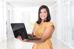 Asian middle aged woman holding an open laptop Stock Images